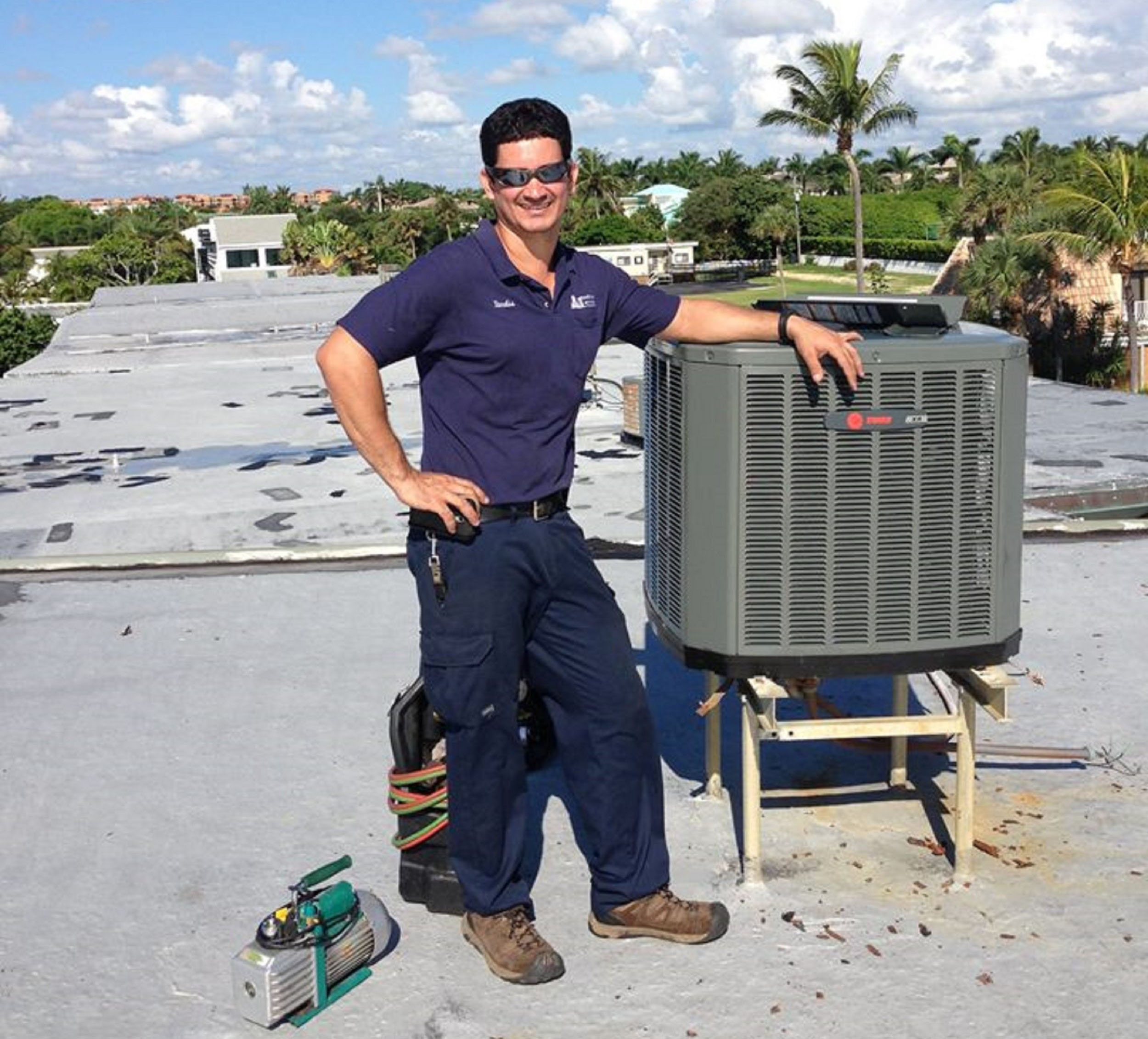 air boca technician posing by outdoor ac unit